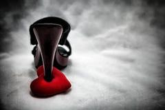 les chaussures de femmes frappent du pied sur le coeur brisé dans le ton foncé , amour non récompensé Photos stock
