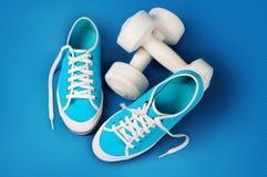 Les chaussures de gymnase de turquoise et les haltères blanches sur un bleu folâtre le tapis Photographie stock libre de droits