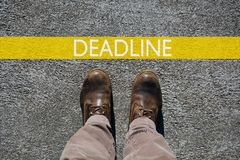 Les chaussures de l'homme regardent de la date-butoir ci-dessus, de mot et d'une ligne de limite jaune avec l'espace de copie images stock