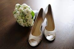 Les chaussures de la mariée avec une pièce de monnaie chanceuse Photos stock