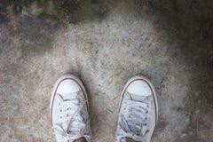 Les chaussures de toile blanches sur le ciment ont rectifié avec l'espace de copie abrégez le fond Photographie stock libre de droits