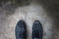 Les chaussures de toile noires sur le ciment ont rectifié avec l'espace de copie abrégez le fond Photographie stock