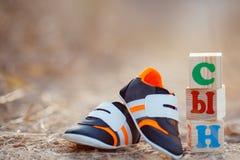 Les chaussures des enfants et le fils de mot Photo stock