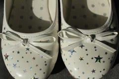 Les chaussures des girlblancs avec les étoiles argentées Image stock