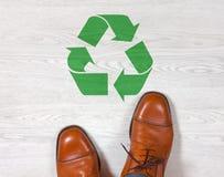 Les chaussures des hommes classiques avec un symbole de réutilisation sur le plancher Photo stock