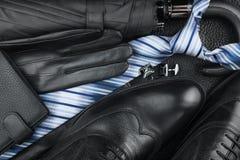 Les chaussures des hommes classiques, lien, boutons de manchette, gants, parapluie sur la peau naturelle Photos stock