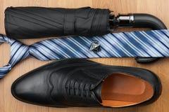 Les chaussures des hommes classiques, lien, parapluie, boutons de manchette sur le plancher en bois Photos stock