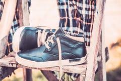 Les chaussures des hommes, enveloppées dans une écharpe sur une échelle en bois Image stock