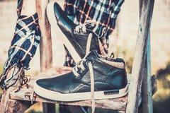 Les chaussures des hommes, enveloppées dans une écharpe sur une échelle en bois Images stock