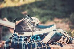Les chaussures des hommes, enveloppées dans une écharpe sur une échelle en bois Photos stock