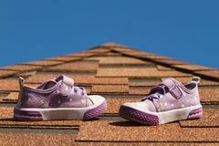 Les chaussures des sports des enfants se tiennent sur le toit de tuile stratifié Photos libres de droits