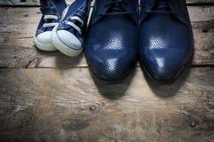 Les chaussures du père et les espadrilles d'enfants côte à côte sur le bois rustique franc Photo stock