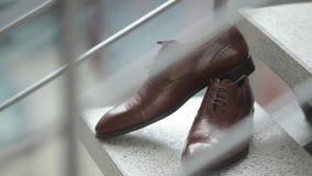 Les chaussures du ` s d'hommes du marié se tiennent sur les étapes le jour du mariage avant la cérémonie solennelle clips vidéos