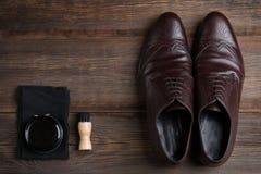 Les chaussures du ` s d'hommes sont brunes avec de la crème de chaussure Soin de chaussure photos libres de droits