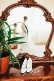 Les chaussures du ` s de jeune mariée se tiennent près du miroir Photo stock