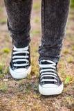 Les chaussures en caoutchouc courantes sont sur des jambes, personne marchant sur terre, verticale Photo stock