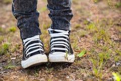 Les chaussures en caoutchouc courantes sont sur les jambes, personne se tenant sur terre Photos libres de droits
