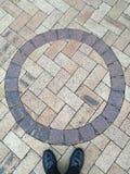 Les chaussures en cuir noires se tenant au-dessous du cercle forment le floo de pavé rond Photos libres de droits
