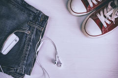 Les chaussures et le smartphone rouges de sports dans des jeans d'une poche sur un blanc courtisent Photos stock