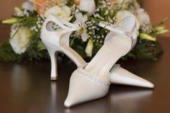 Les chaussures et les fleurs de la jeune mariée Photos stock