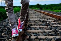 Les chaussures inverses de port de rouge d'homme et la marche sur le chemin de fer treck Images libres de droits