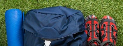 Les chaussures, la couverture et le sac à dos de touristes se trouvent sur l'herbe verte Photo stock