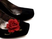 Les chaussures noires de hauts talons avec le rouge se sont levées Photographie stock