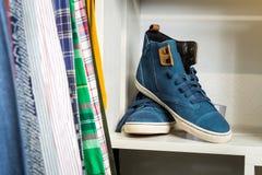 Les chaussures se trouvent sur une étagère dans un magasin de concepteur Images stock