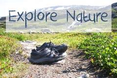 Les chaussures sur le chemin de trekking, texte explorent la nature image stock