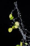 Les chaux avec de l'eau éclabousse sur le fond noir Image libre de droits