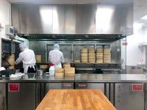 Les chefs font cuire les boulettes chinoises en les vapeurs en bambou traditionnels dans un restaurant photographie stock libre de droits