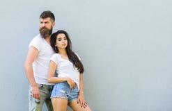 Les chemises blanches de couples caressent près du mur gris Équipement élégant de la jeunesse simple mais moderne Les amis de cou photo libre de droits
