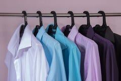 Les chemises d'hommes colorés qui accrochent sur des cintres Image stock