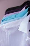 Les chemises d'hommes colorés qui accrochent sur des cintres Photo stock