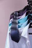 Les chemises d'hommes colorés qui accrochent sur des cintres Photographie stock