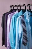 Les chemises d'hommes colorés qui accrochent sur des cintres Photos stock