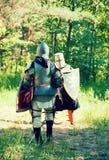 Les chevaliers dans l'armure combat à la forêt Photographie stock libre de droits