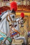 Les chevaux dans un joyeux vont rond Images stock