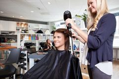 Les cheveux de Drying Customer de coiffeur images libres de droits