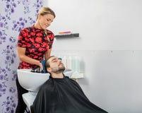 Les cheveux de Drying Male Customer d'esthéticien dans le salon photos libres de droits