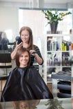 Les cheveux de la femme de séchage de styliste images stock