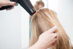 Les cheveux de la femme de séchage de styliste Photo stock