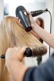 Les cheveux de la femme de séchage de styliste dans le coiffeur Salon images libres de droits