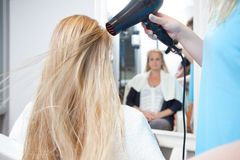 Les cheveux de la femme de séchage de styliste dans le salon de beauté photographie stock