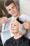 Les cheveux de Setting Up Client de coiffeur image stock