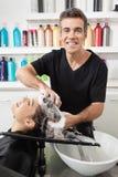 Les cheveux du client de lavage de styliste en coiffure au salon photo libre de droits