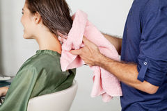 Les cheveux du client de séchage de styliste en coiffure au salon images libres de droits