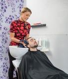 Les cheveux du client masculin de séchage de styliste en coiffure dans le salon photo libre de droits