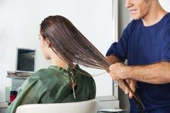 Les cheveux humides de Combing Client masculin de coiffeur Images stock