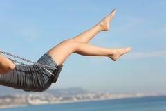 Les cheveux ont enlevé des jambes de femme balançant sur la plage Photos stock